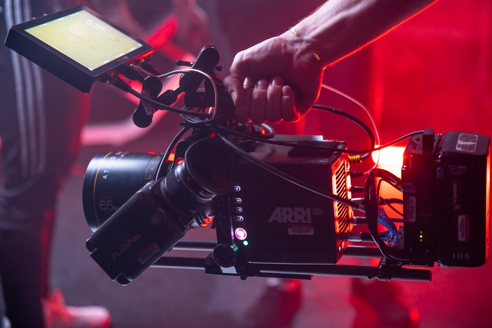 person holding black and red video camera