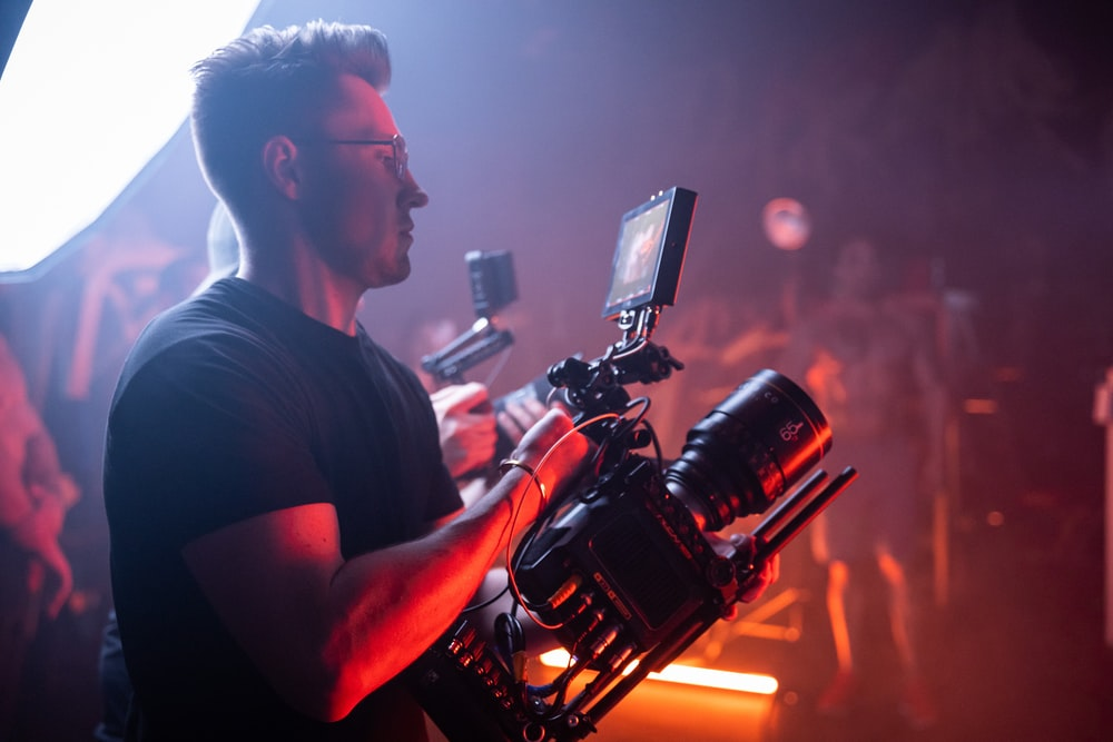 man in black crew neck t-shirt holding black video camera