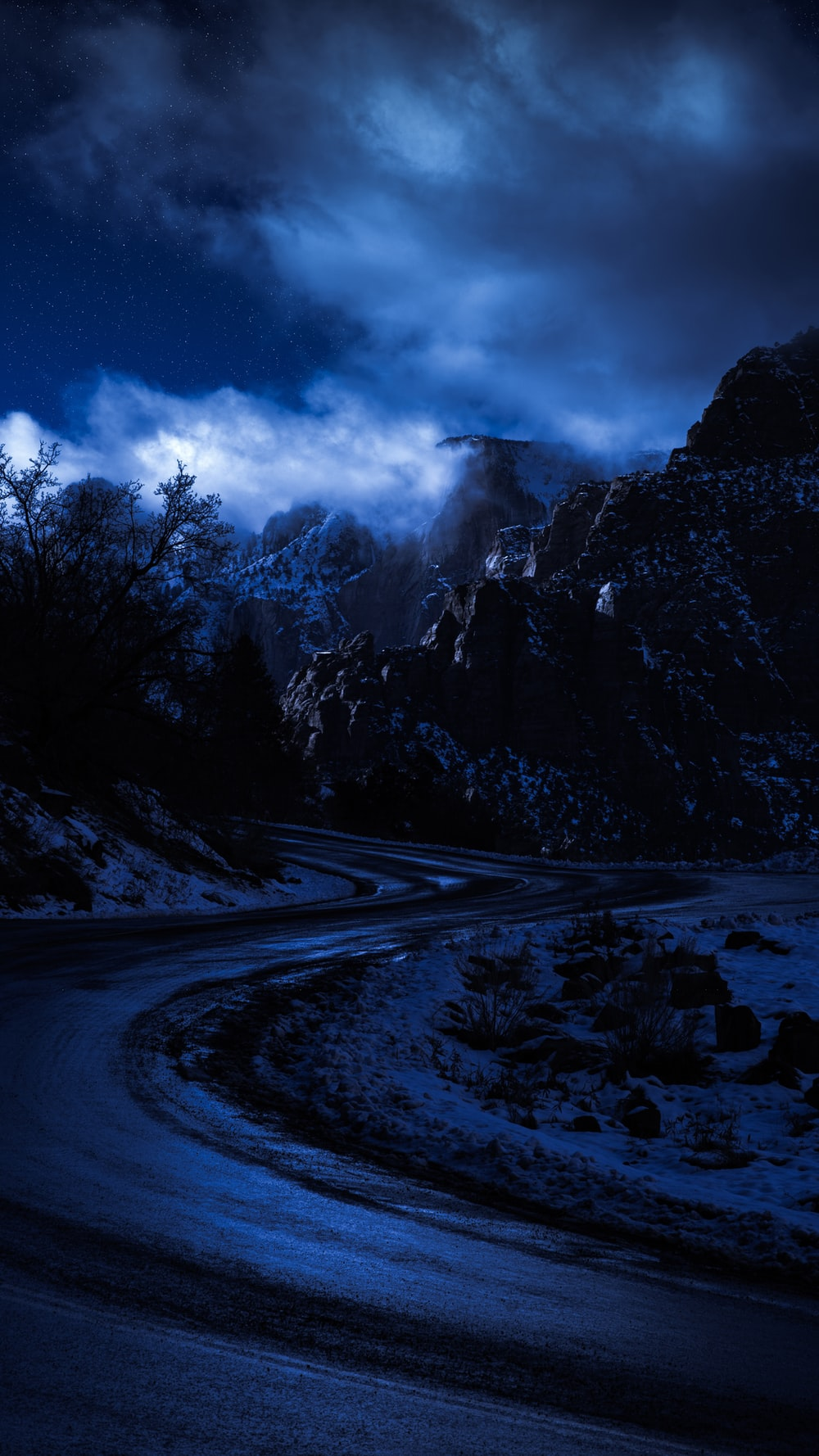 snow covered road near trees and mountain under cloudy sky during daytime