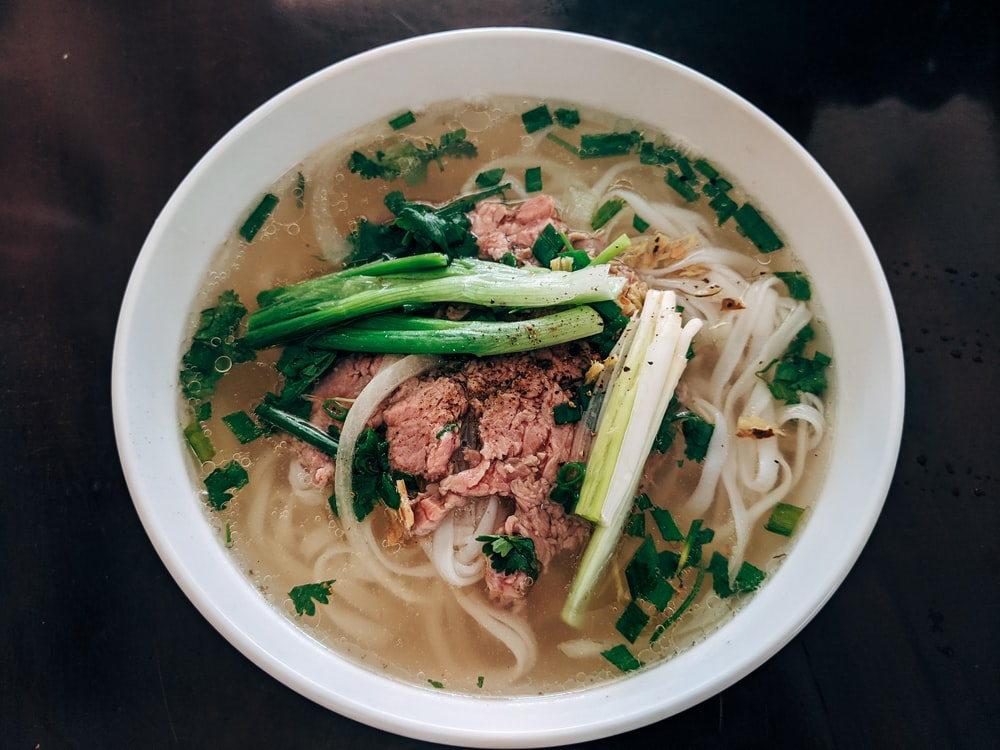 white noodle soup with green leaf vegetable in white ceramic bowl