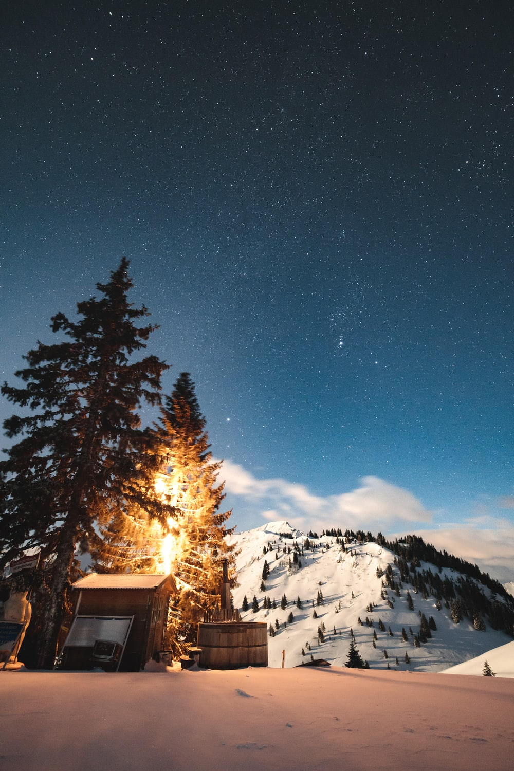 brown wooden house on snow covered ground near trees under blue sky during night time