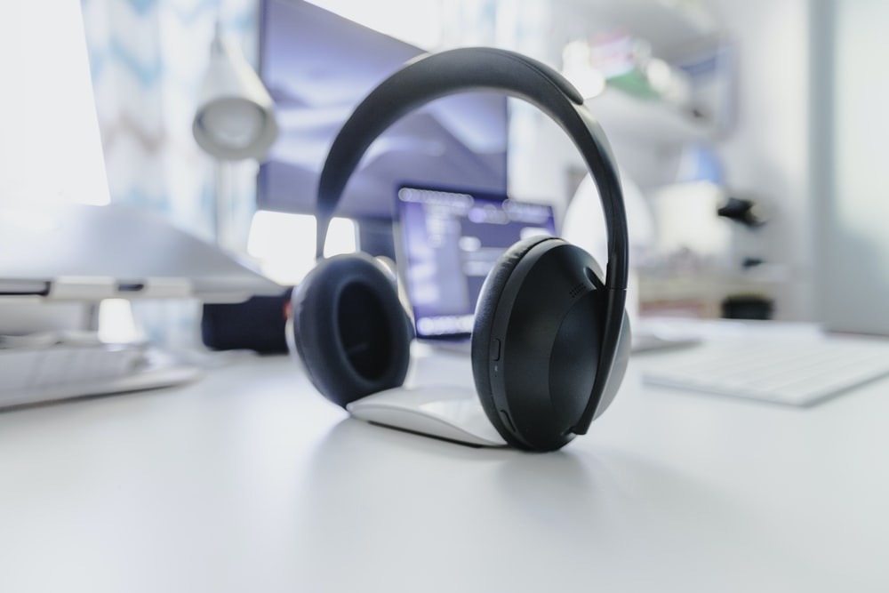 black and gray wireless headphones on white table