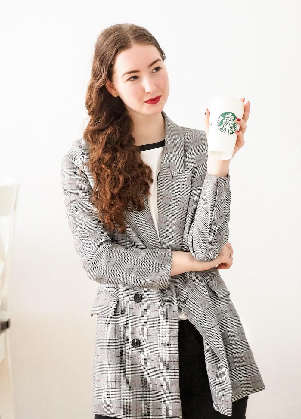 woman in gray coat holding white ceramic mug
