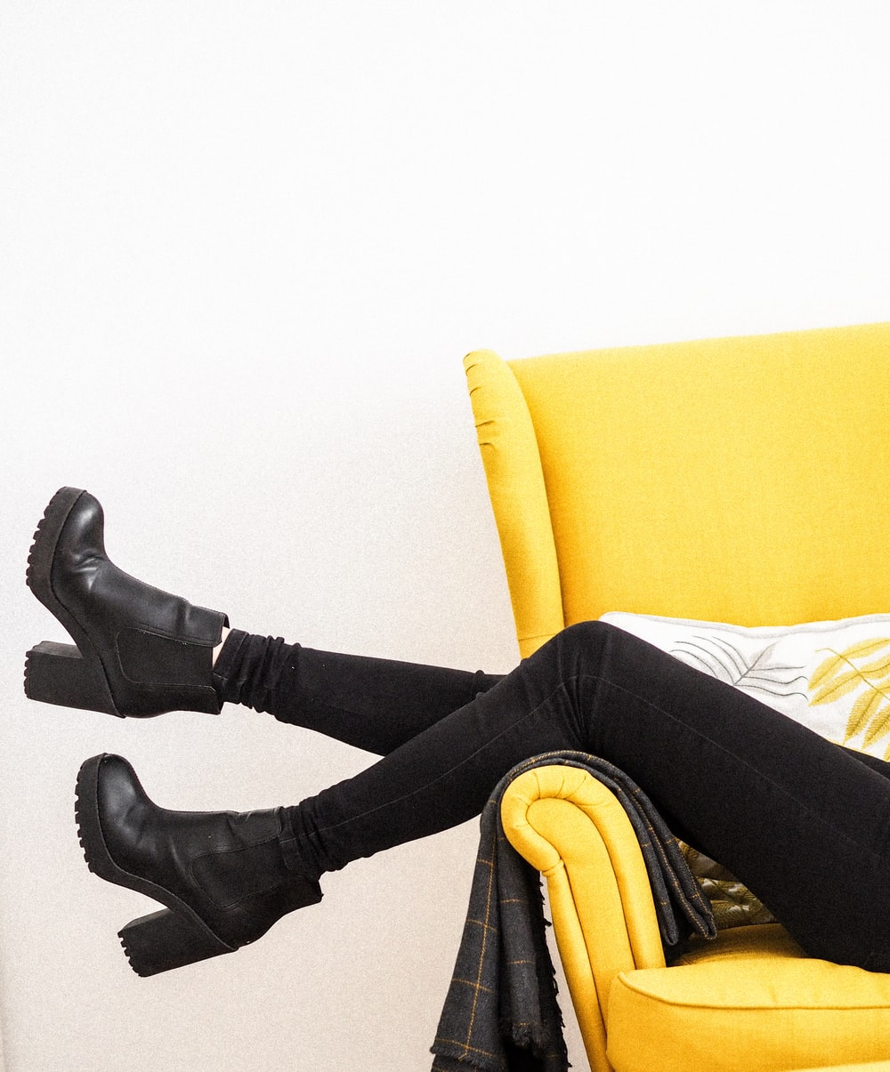 person in black leather boots sitting on yellow sofa