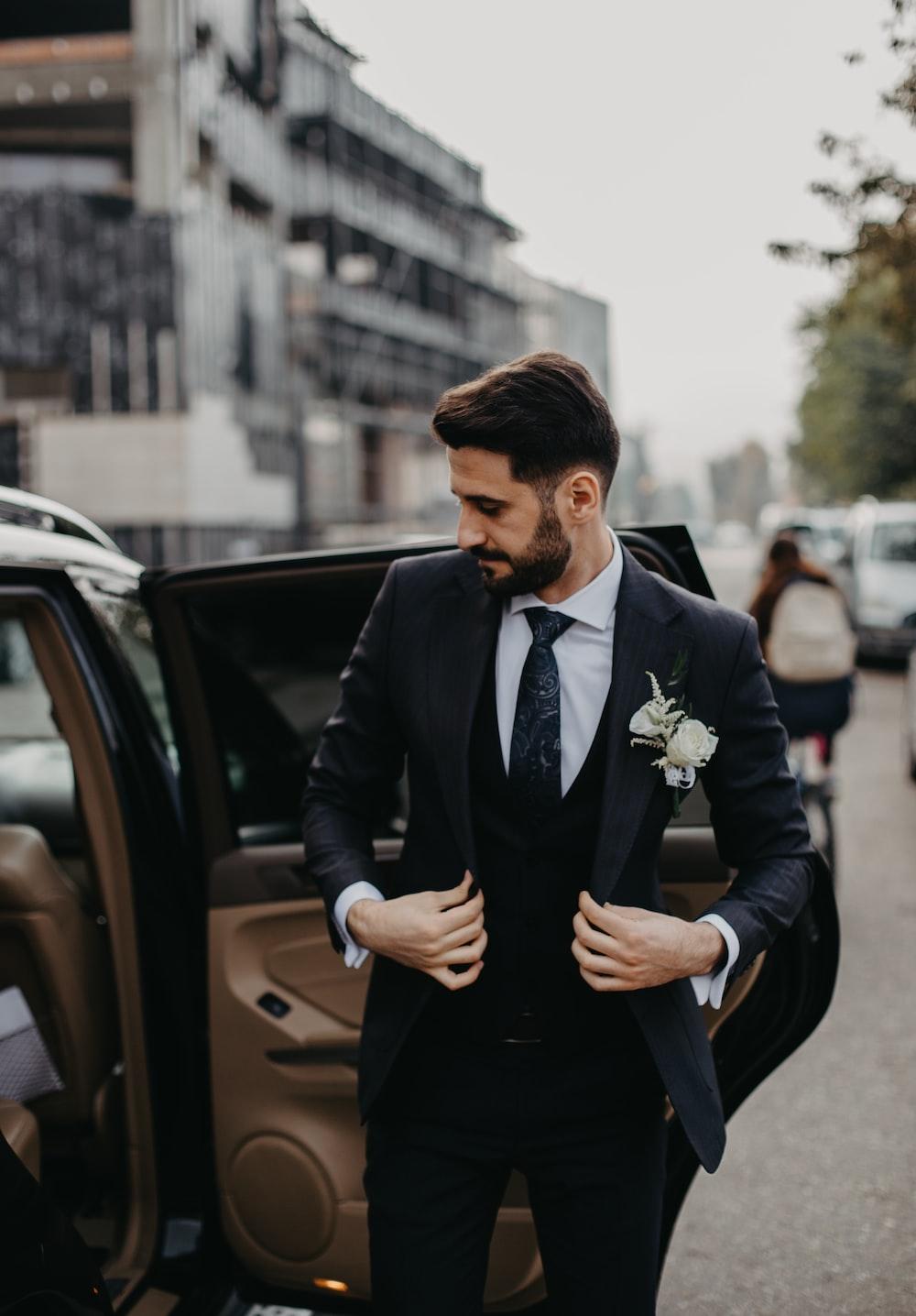 man in black suit jacket and black pants sitting on black car