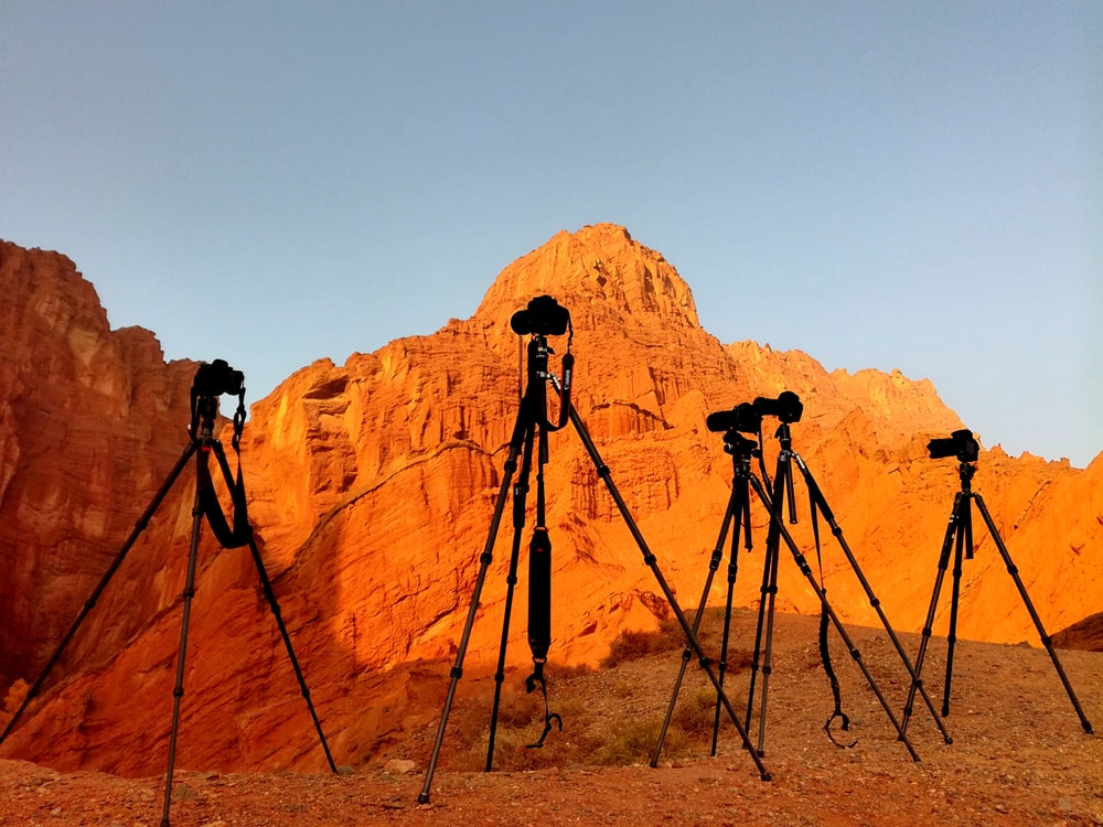 black camera on tripod on brown rock formation during daytime