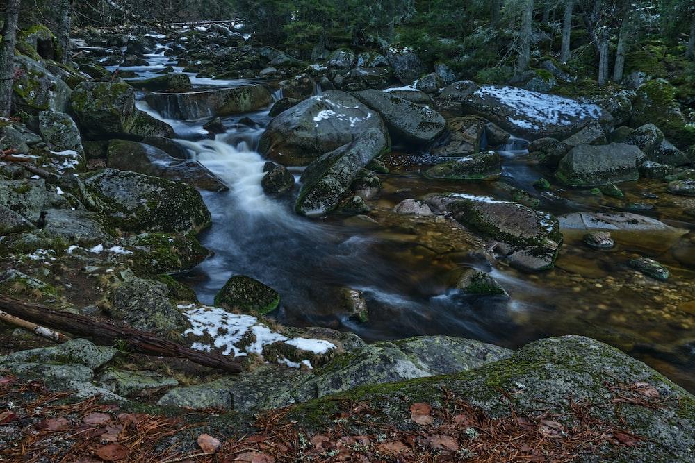 water flowing on rocks during daytime