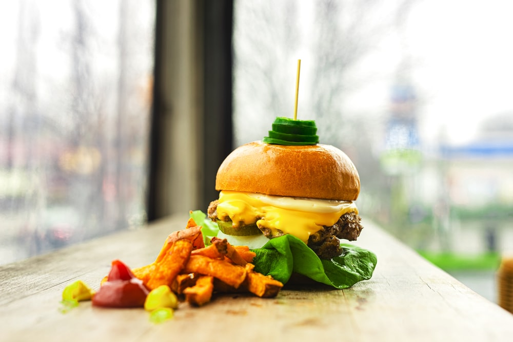 burger with lettuce and tomato on white ceramic plate