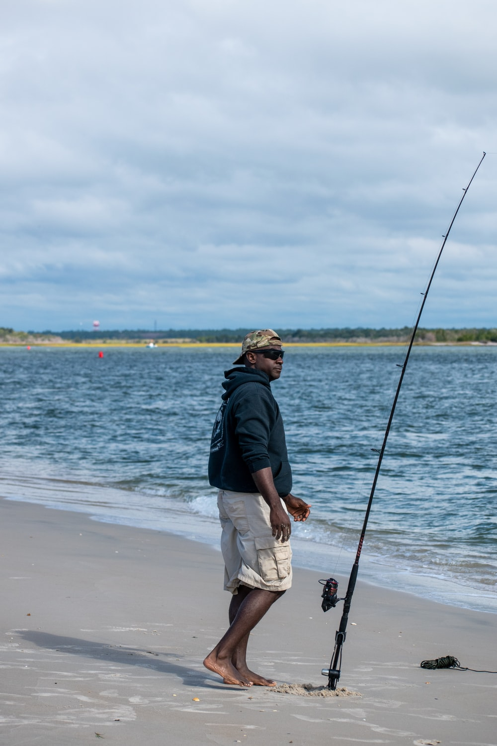 man in black shirt and white shorts fishing on sea during daytime