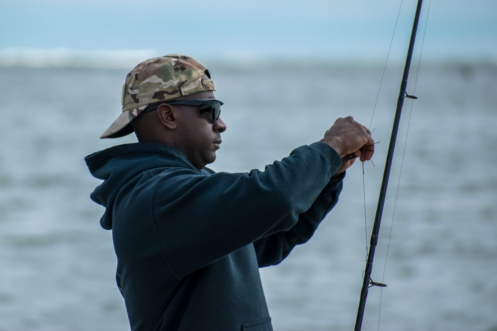 man in black jacket and brown and beige camouflage cap holding fishing rod