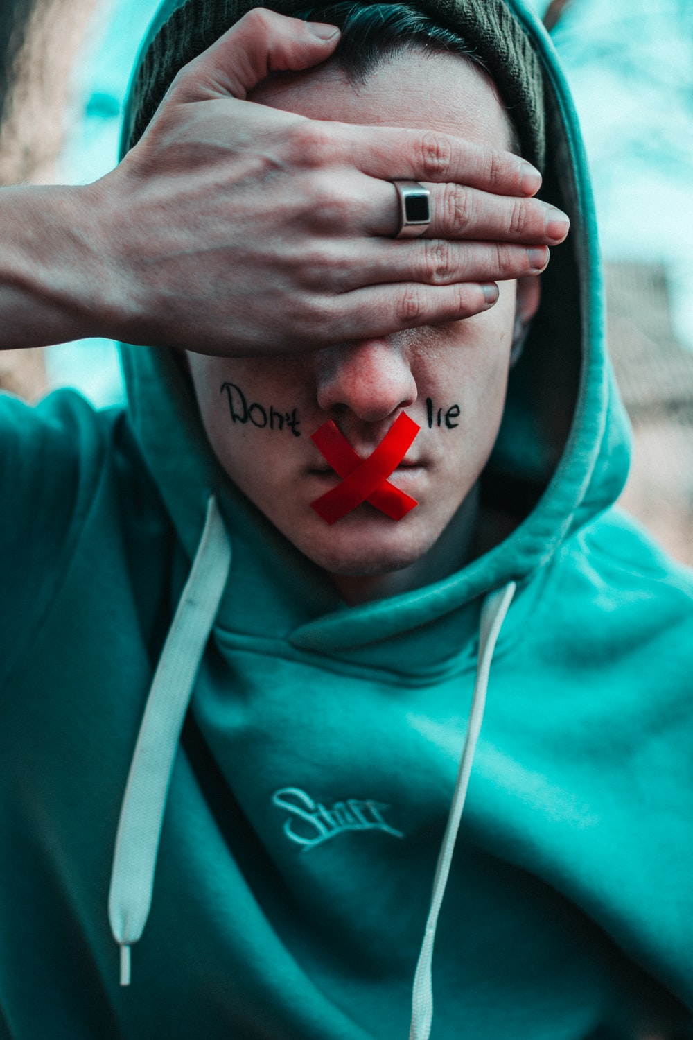 man in teal hoodie with i love you text