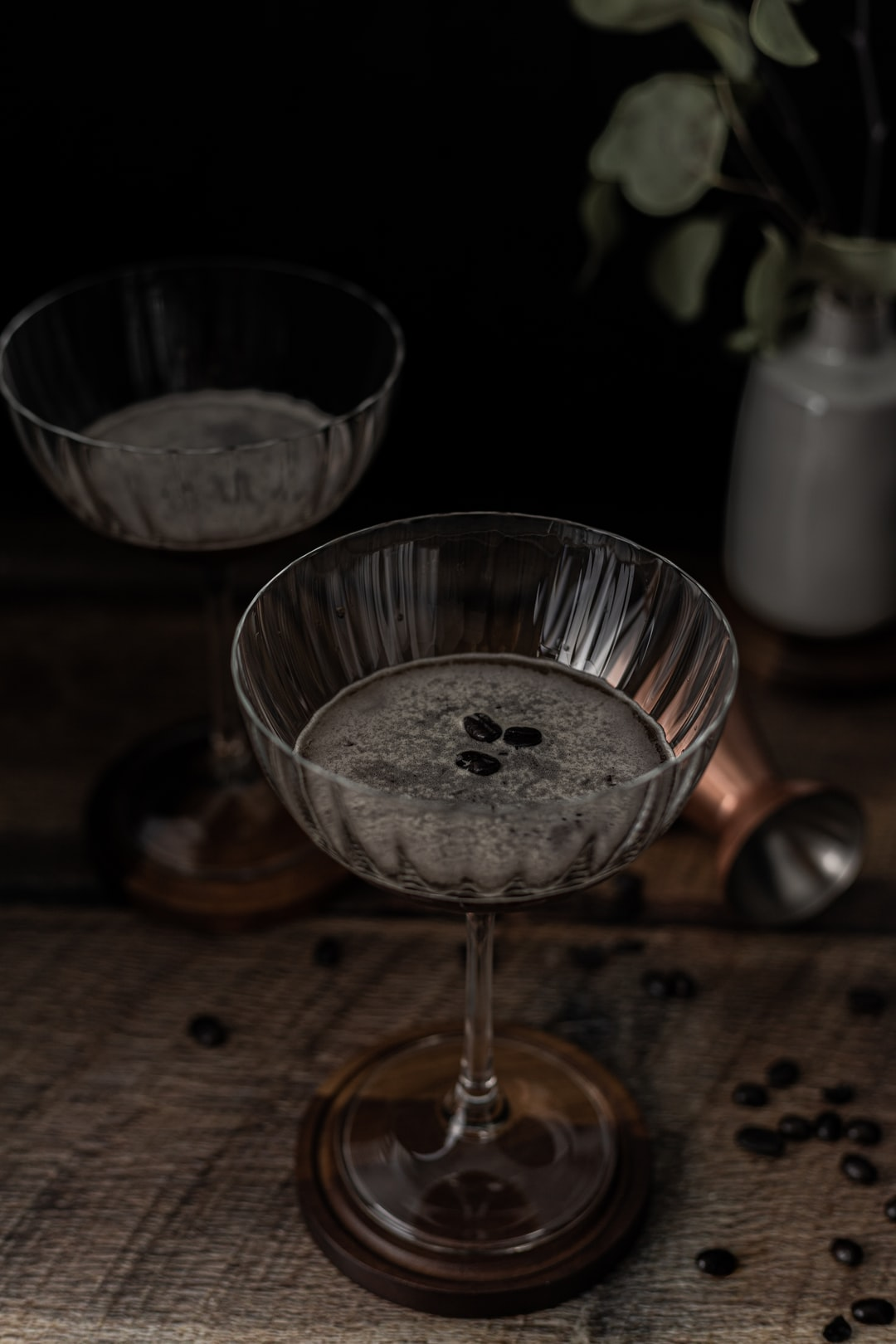 Coffee cocktail with coffee beans and plant on wood