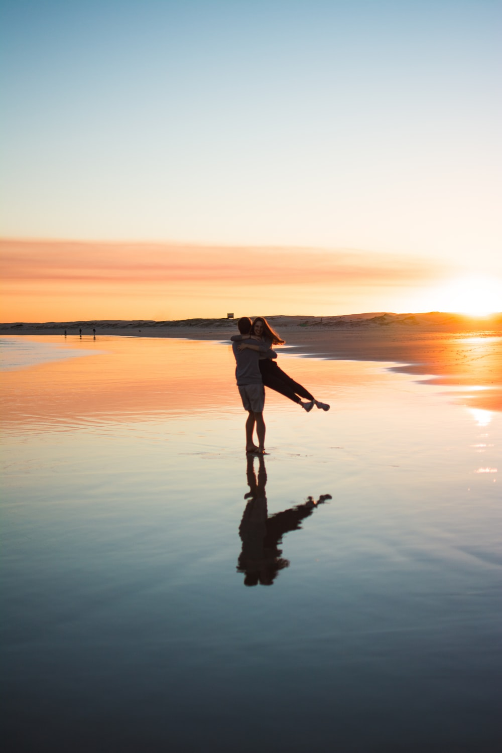 man in black jacket and pants standing on shore during sunset