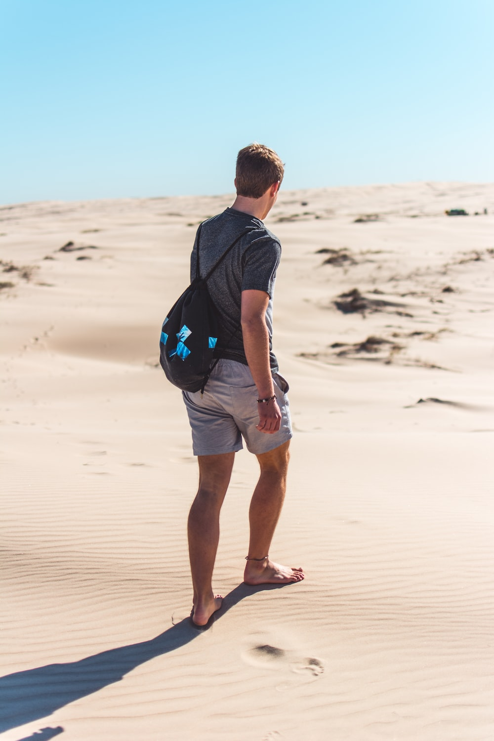 man in black long sleeve shirt and blue shorts walking on sand during daytime