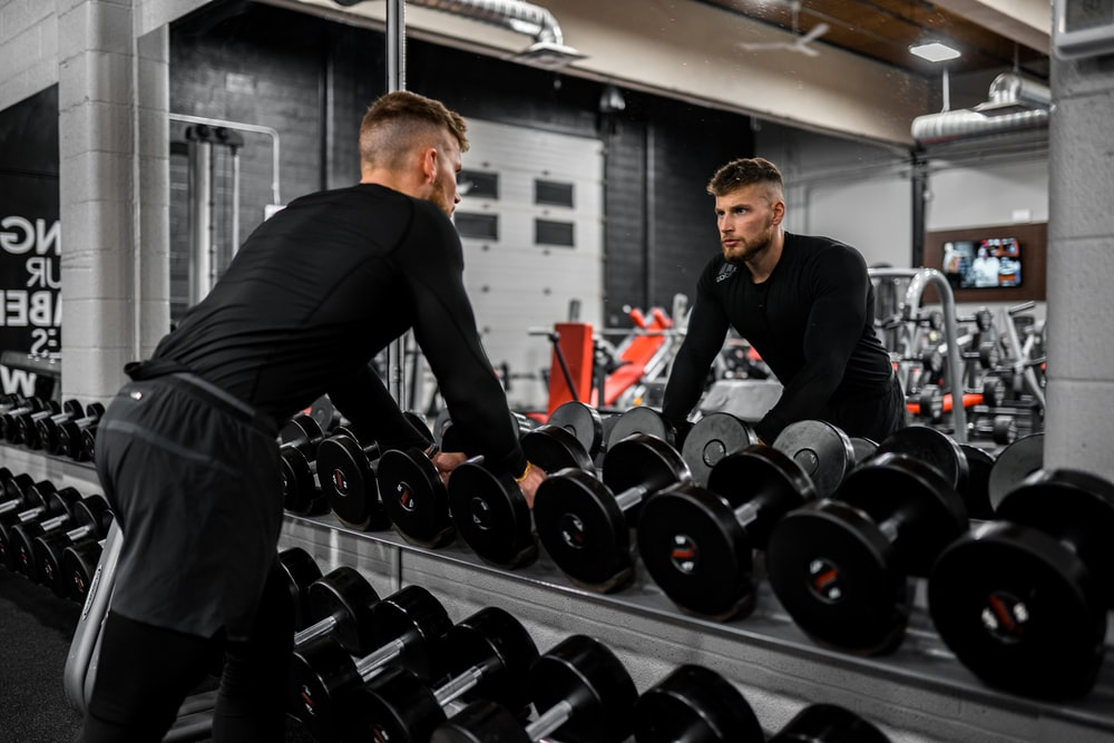 man in black long sleeve shirt and black pants carrying black dumbbell