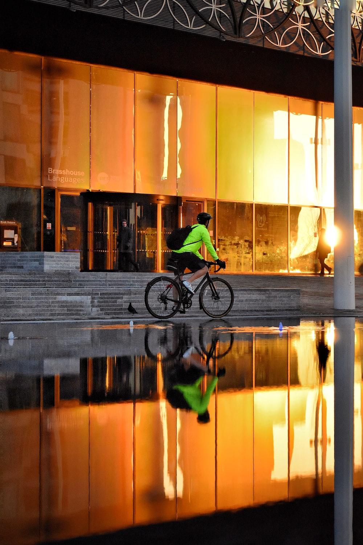 man in green jacket riding bicycle