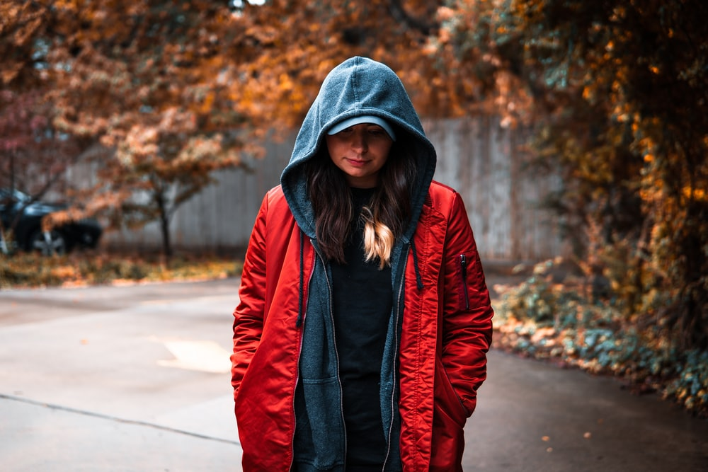 woman in red and black jacket standing on road during daytime