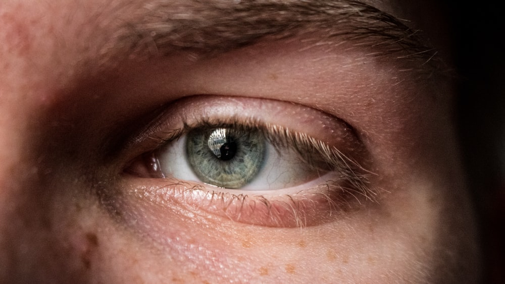 persons blue eye in close up photography