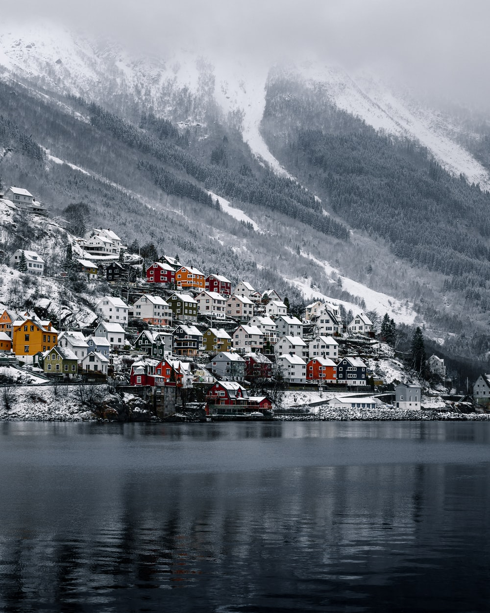 houses near body of water and snow covered mountain during daytime