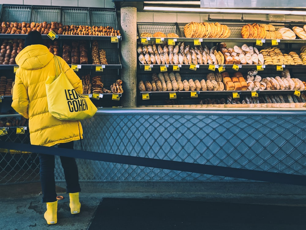man in yellow and black nike jersey shirt standing in front of display counter