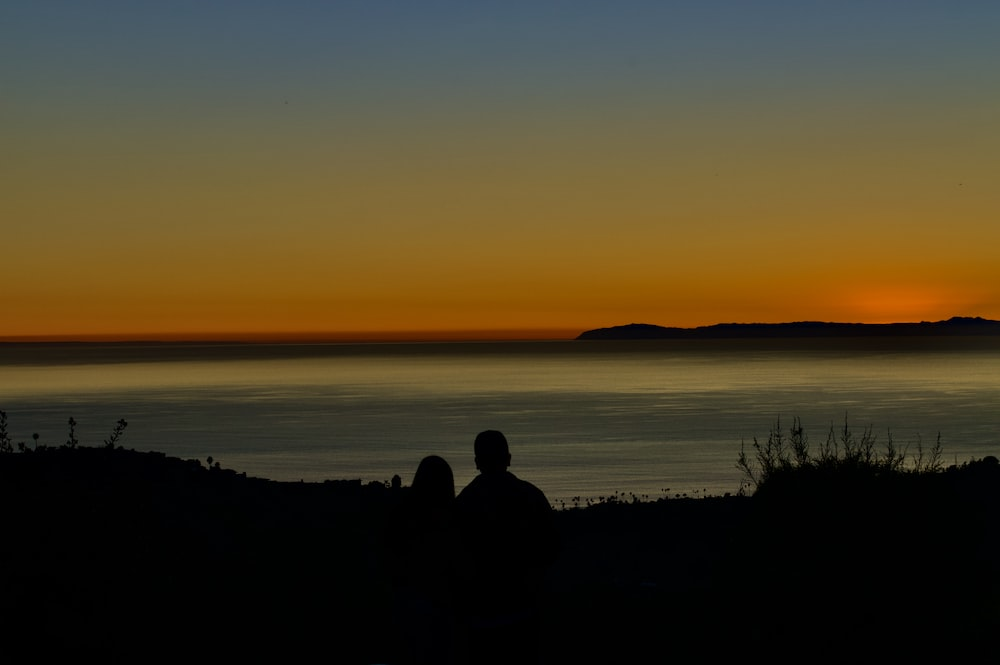 silhouette of 2 person sitting on rock near body of water during sunset