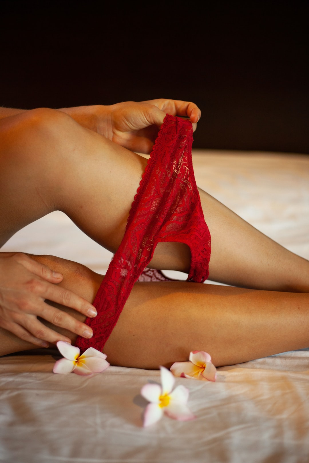 A closeup of a hot girl legs and red panties in suggestive erotic manner. Background with a bed and flowers.