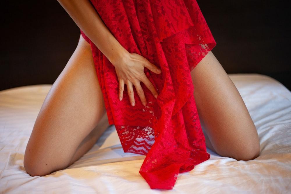ベッドに横になっている赤いレースのドレスを着た女性