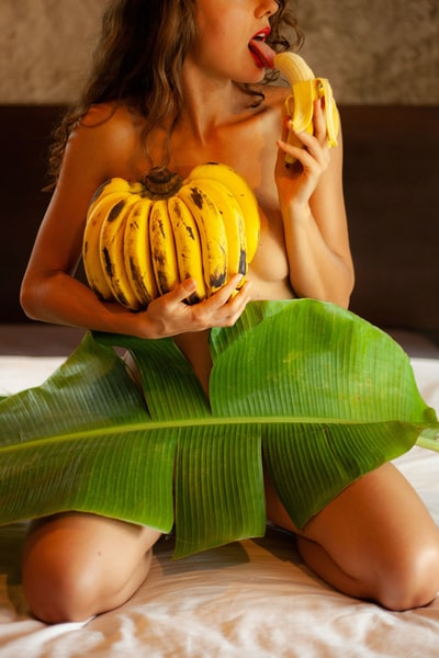 A topless sexy girl covered only with bananas and banana leave.