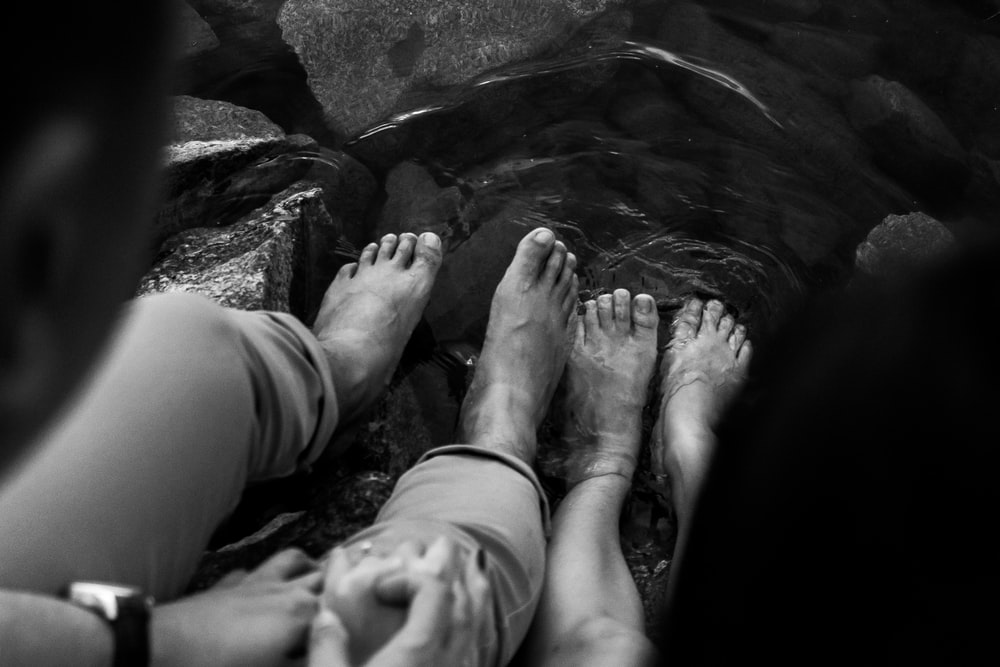grayscale photo of persons feet on water