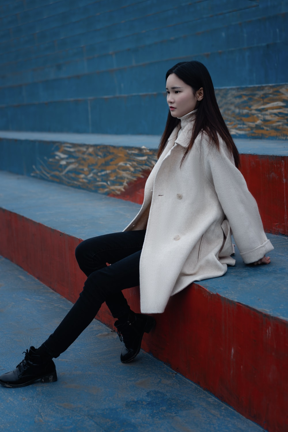woman in white coat and black pants sitting on red concrete bench