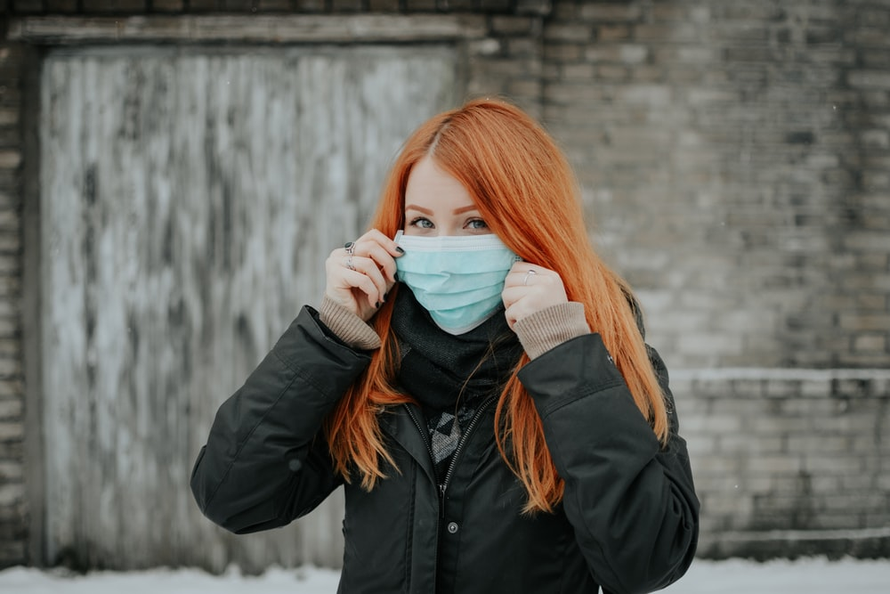 woman in black jacket covering her face with white ceramic mug