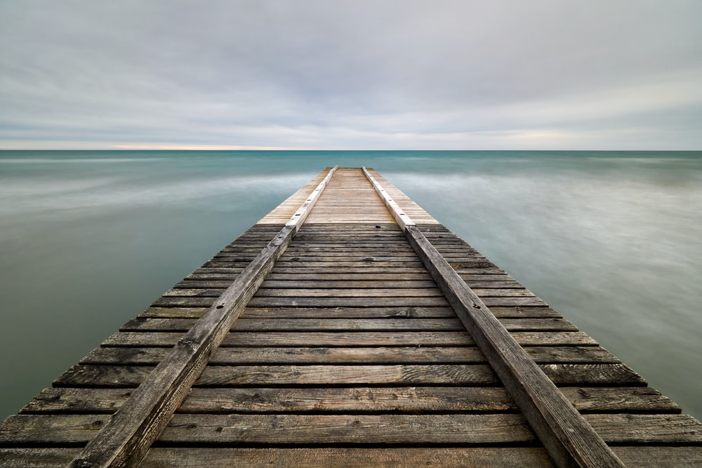 brown wooden dock on body of water under cloudy sky during daytime