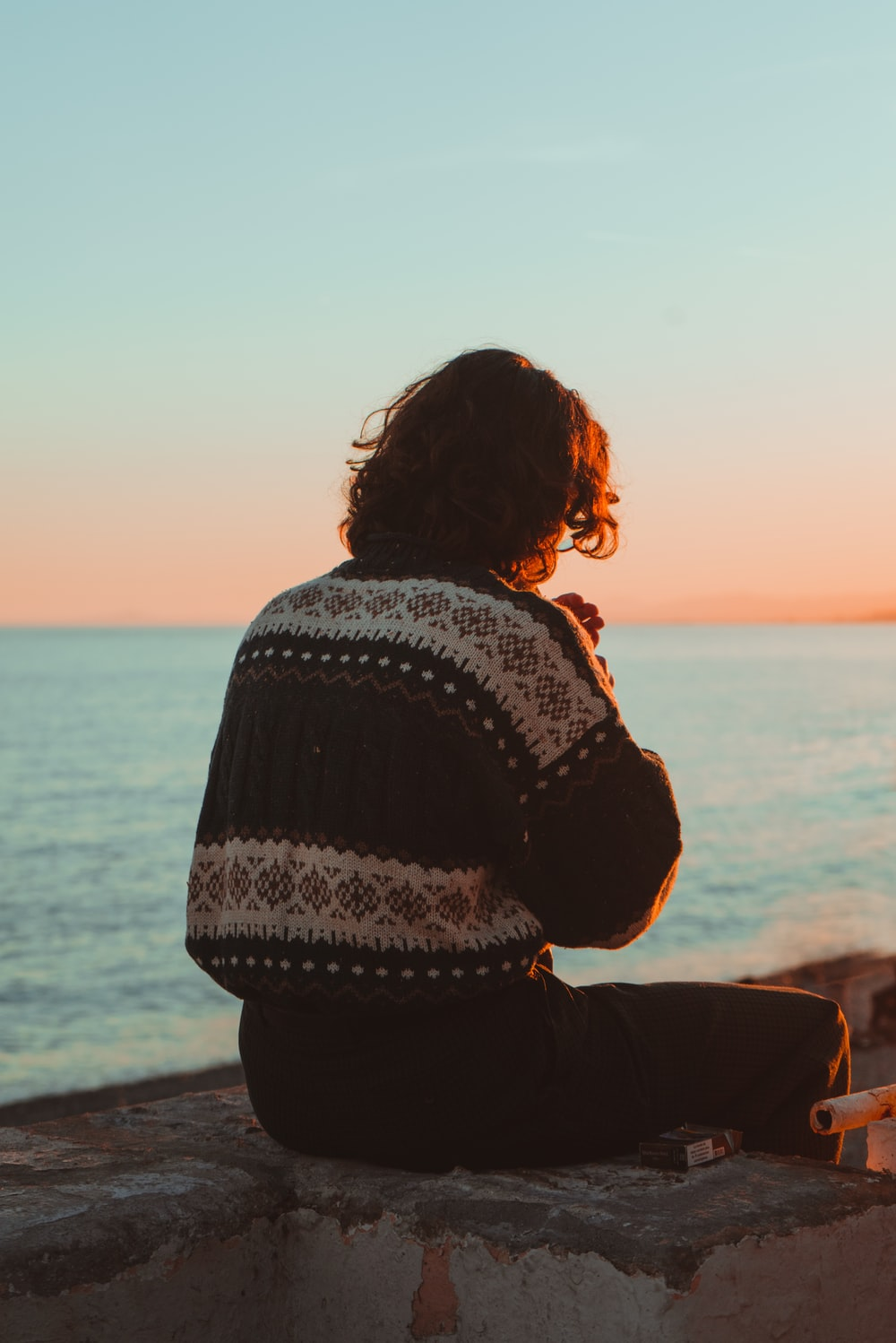 person in black and white sweater sitting on beach shore during sunset