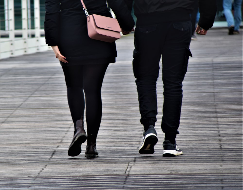 woman in black pants and black leather boots holding brown leather sling bag