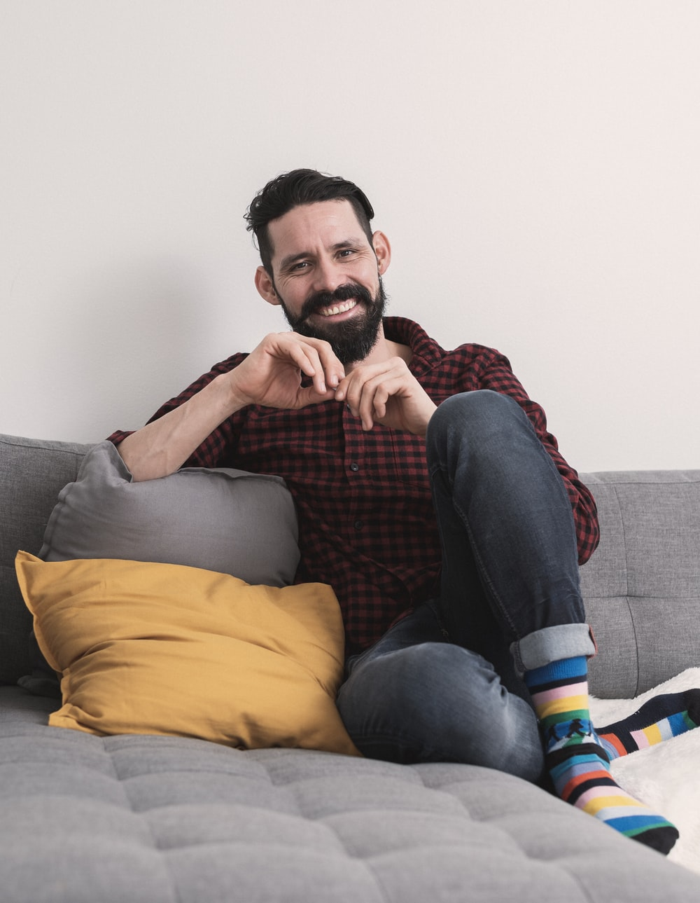 man in gray crew neck t-shirt and blue denim jeans sitting on gray sofa