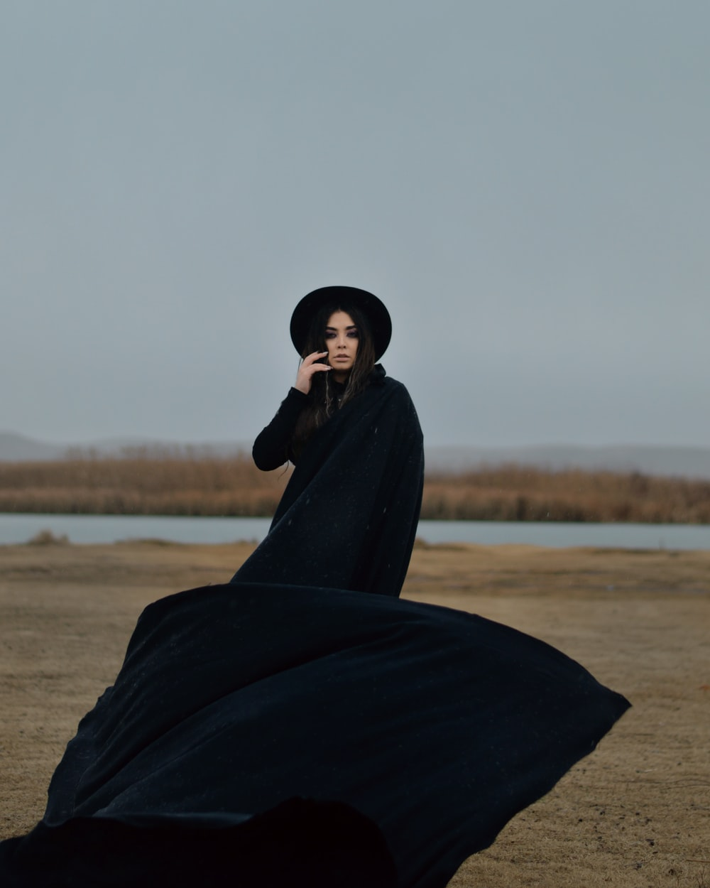 woman in black robe standing on brown field during daytime