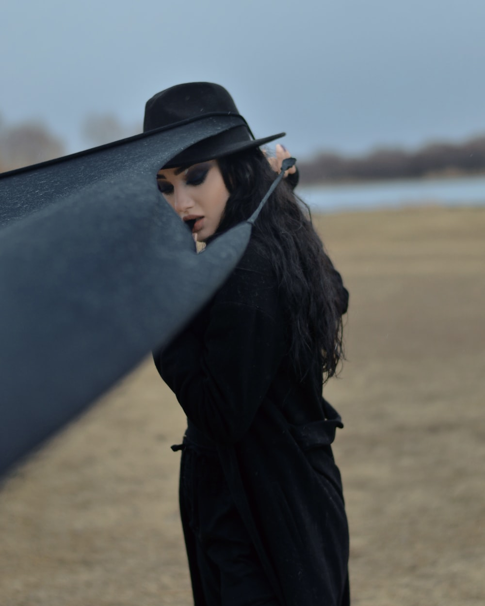 woman in black coat and black hat standing on brown field during daytime