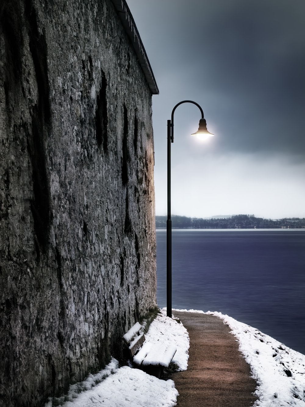 black street lamp near body of water during daytime