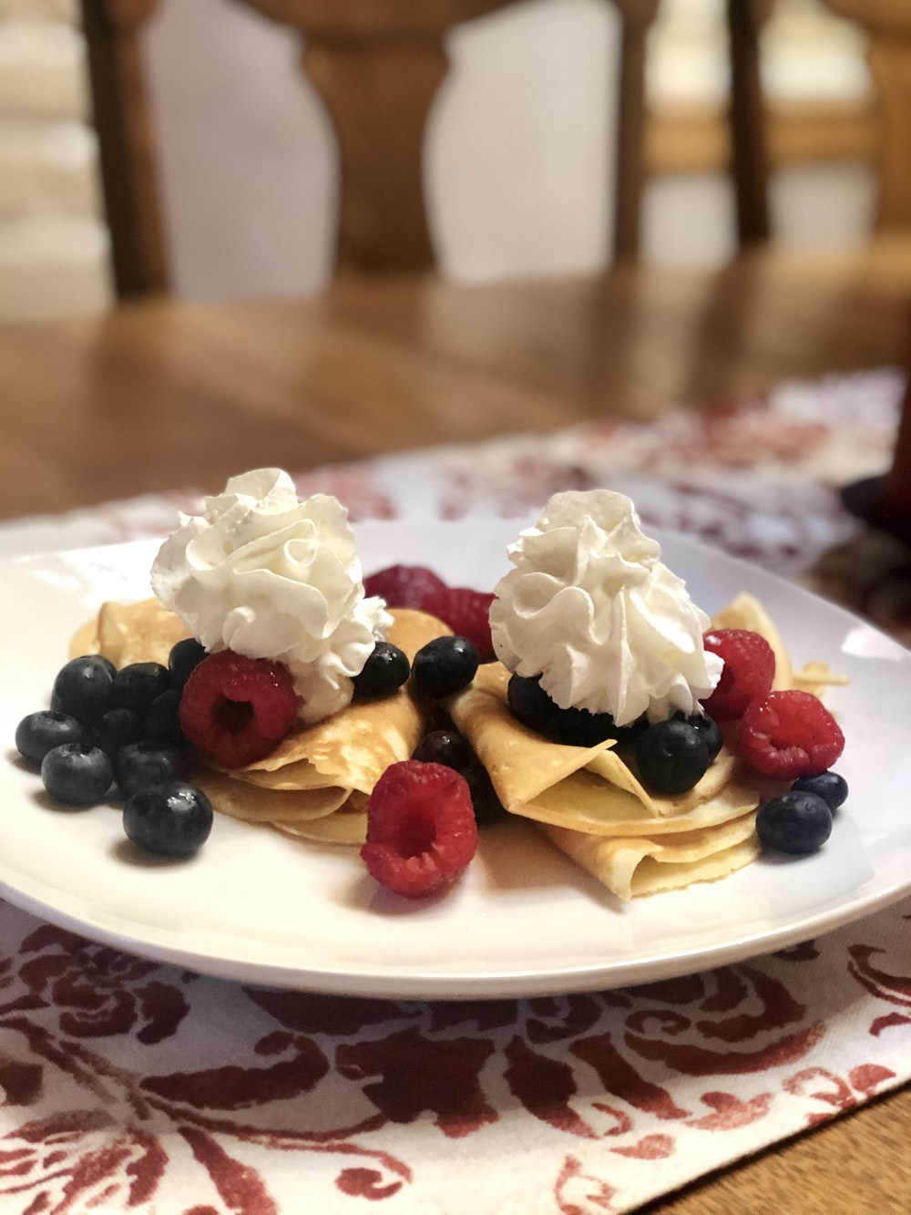white and red ceramic plate with white cream and black berries