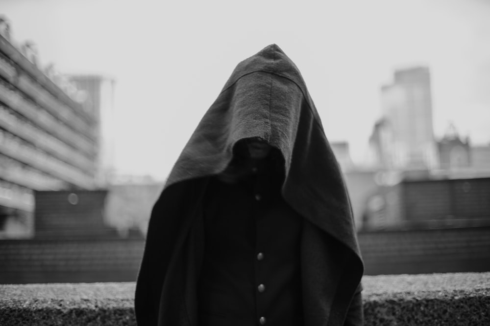 grayscale photo of person covered with blanket