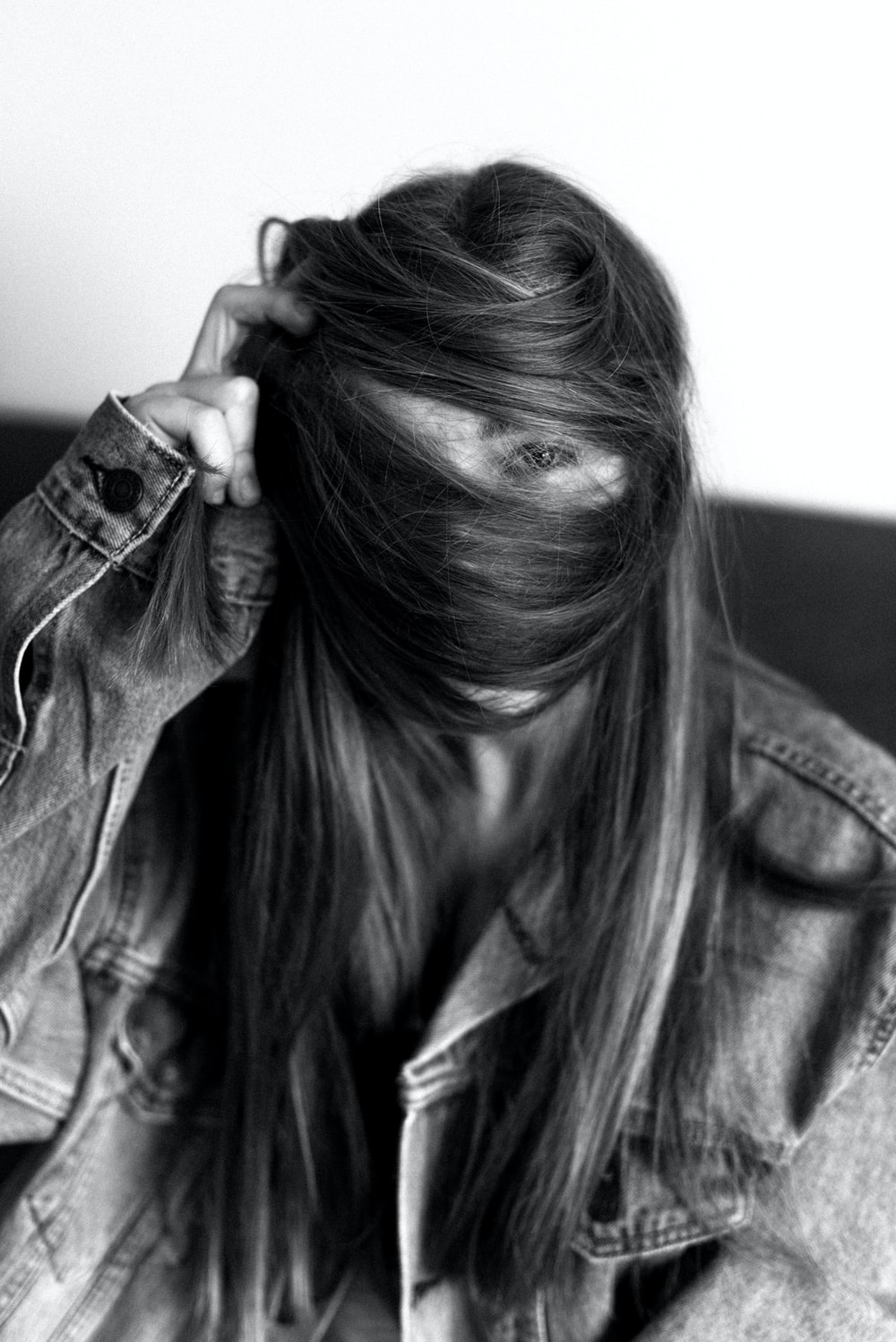 woman in denim jacket covering her face with her hair