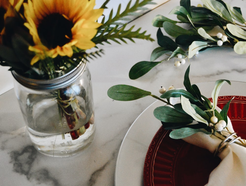 yellow sunflower in clear glass vase
