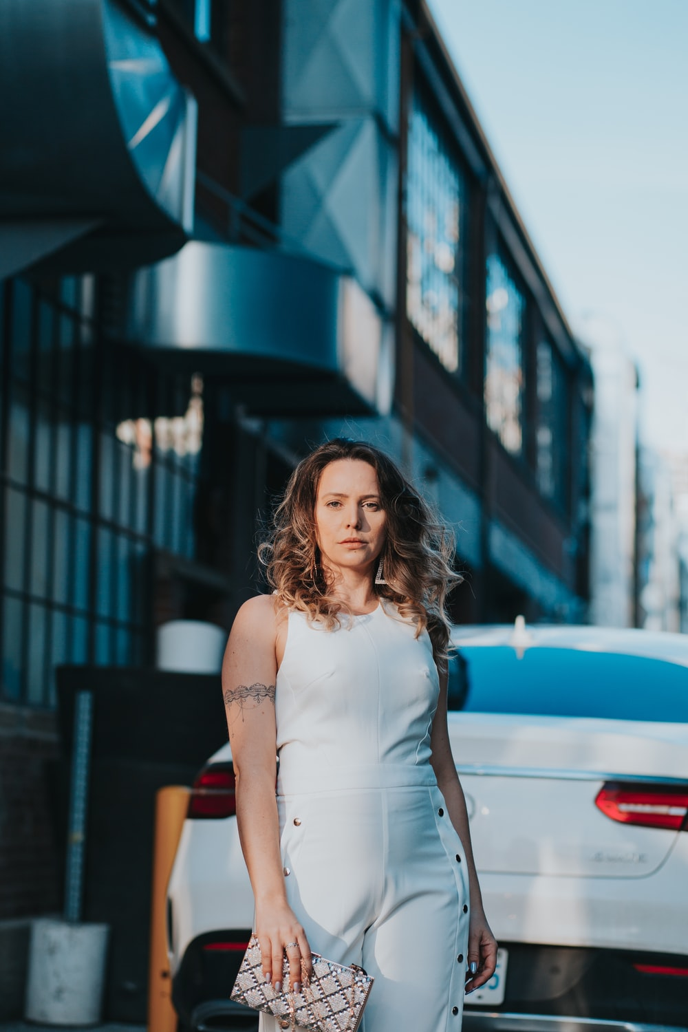woman in white sleeveless dress standing near red car during daytime