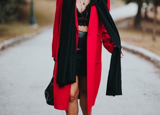 woman in red coat standing on road during daytime