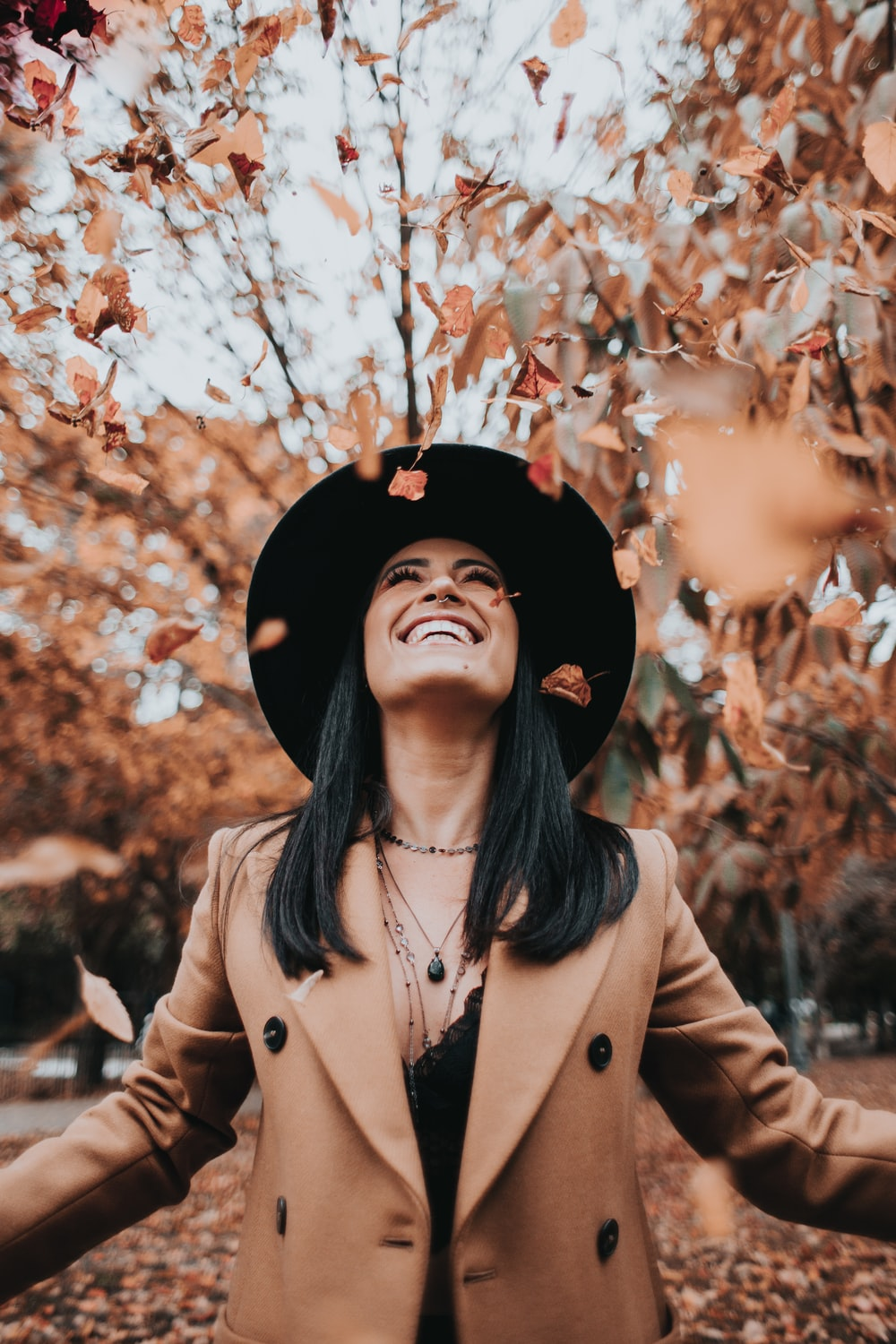 woman in brown coat and black hat standing under brown leaves tree during daytime