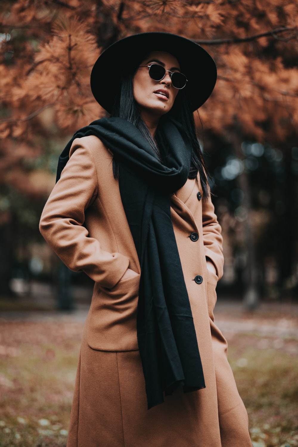 woman in brown coat and black hat standing near brown trees during daytime