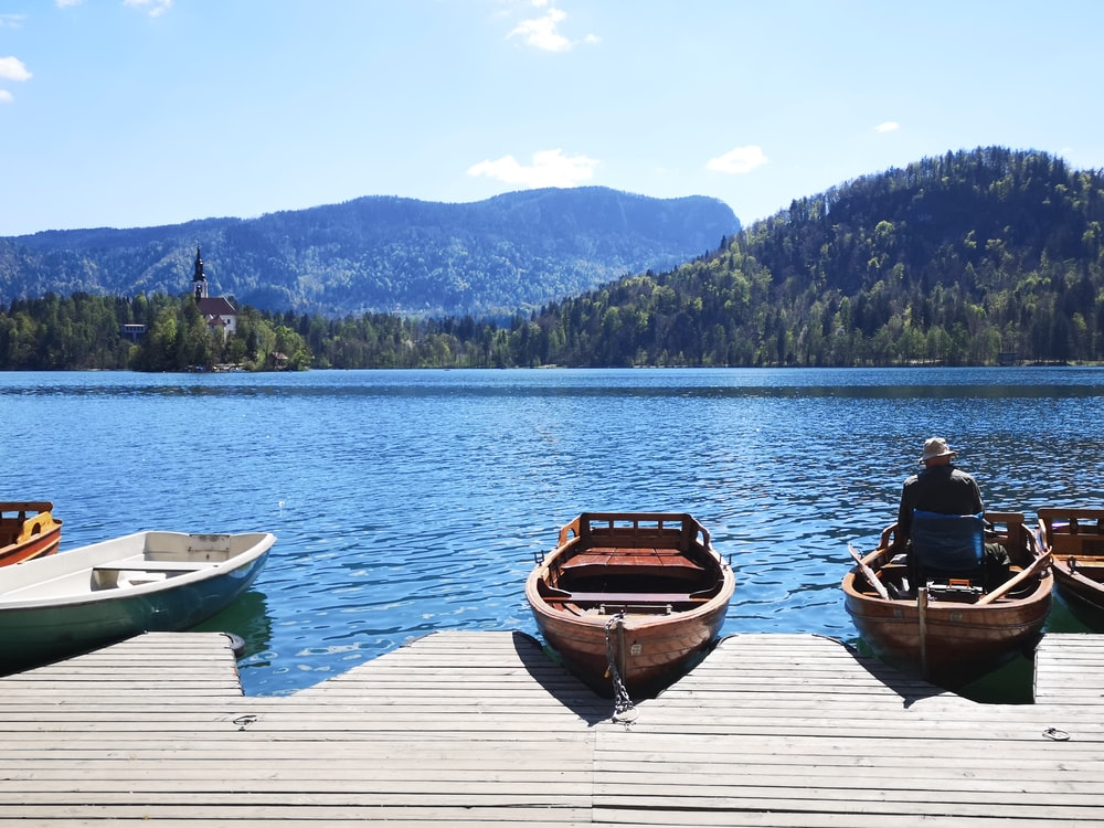 man and woman sitting on brown wooden boat on lake during daytime