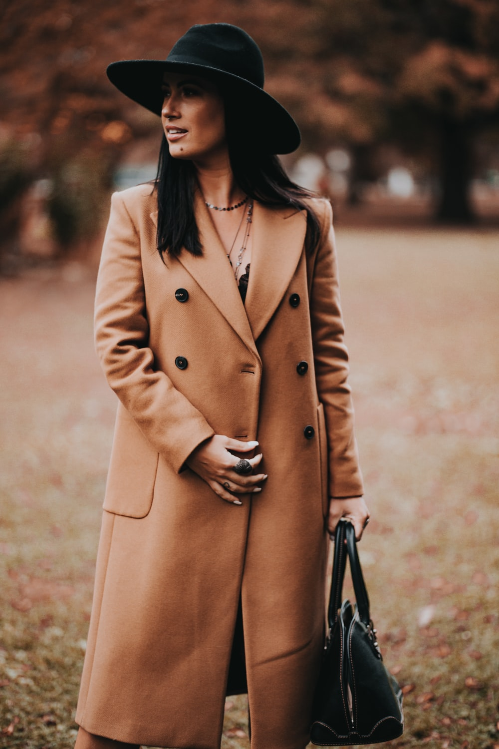 woman in brown coat standing on brown field during daytime
