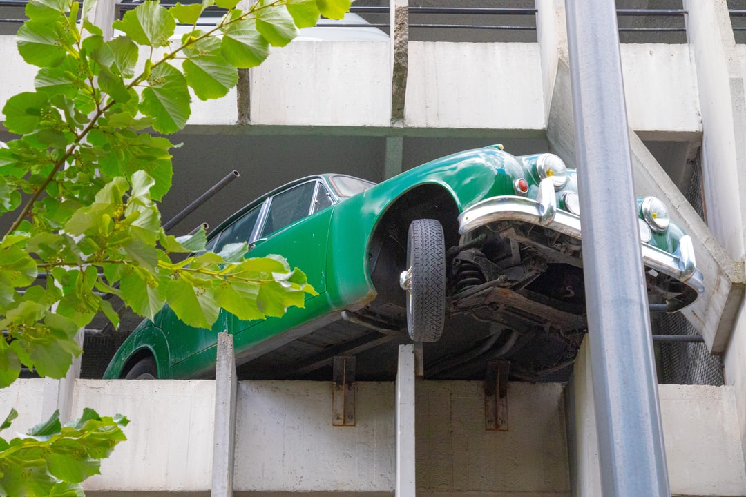 Green car in a multi-story car parking in the city of Bordeaux.