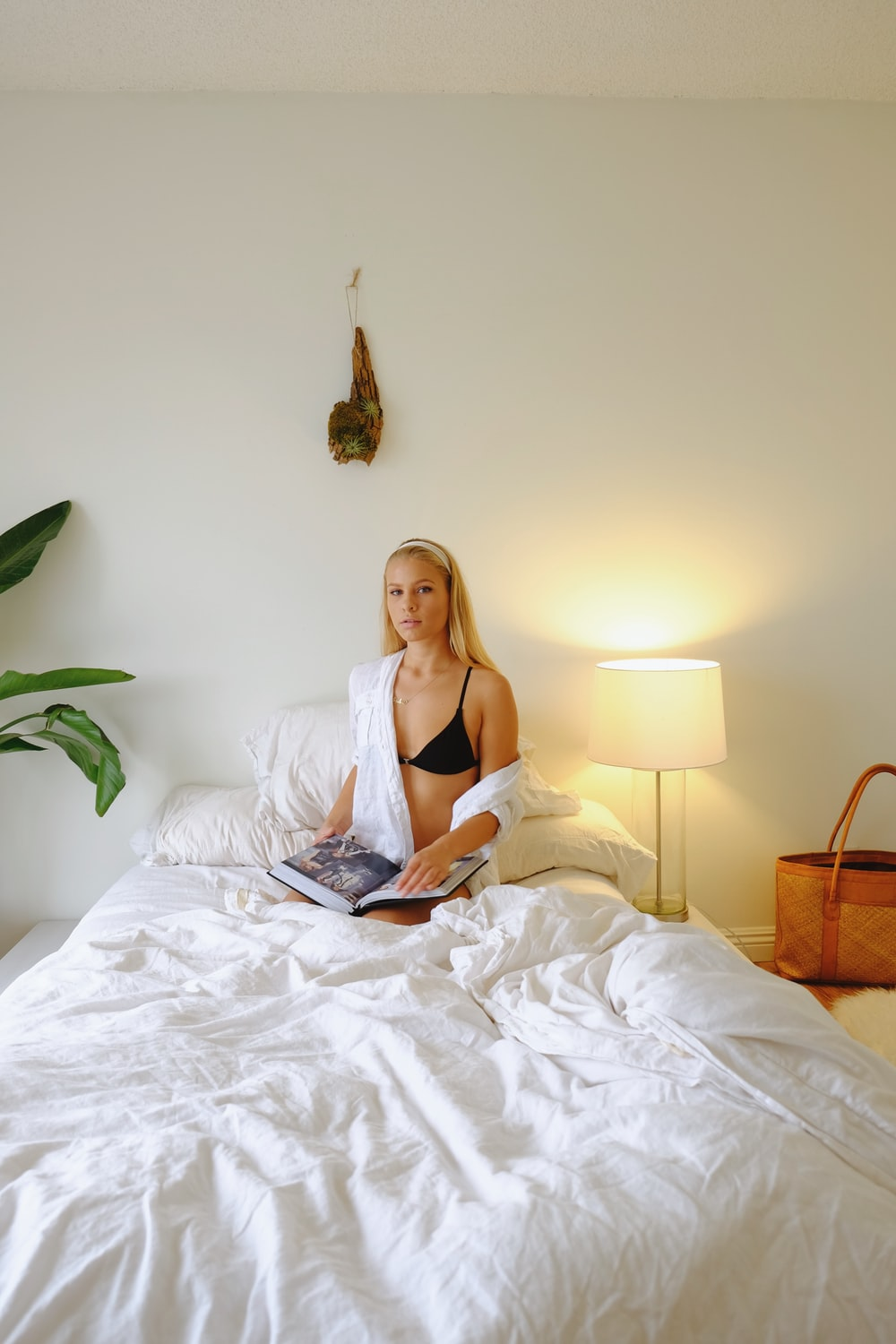 woman in white brassiere lying on bed